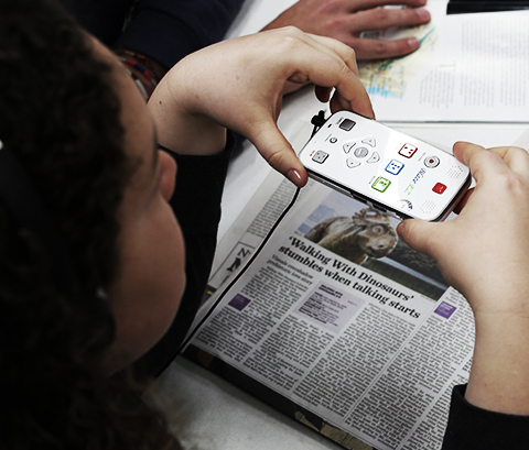 Person reading a newspaper with the Blaze media player.